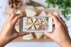 Kvinnahänder som tar ett foto av olika sorter av läcker ost med muttrar arkivfoton