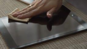 Kvinnahänder som torkar yttersida, avskärmar minnestavladatoren med torkdukeslut upp arkivfilmer