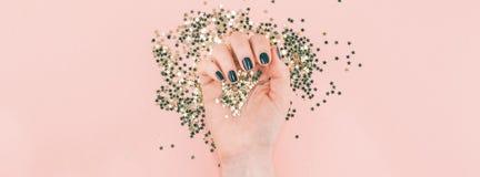 Kvinnahänder täckte guld- stjärnakonfettier på rosa färger royaltyfria foton