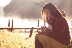 Kvinnahänder vek i bön på en helig bibel för tro arkivfoto