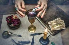 Kvinnahäxan förbereder en magisk dryck cards tarot Framtida läsning Begrepp för förmögenhetkassör royaltyfri bild