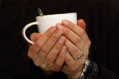 Kvinnahåll per den varma koppen kaffe Arkivbild
