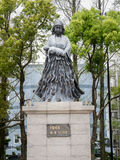 Kvinnahållen behandla som ett barn i hennes arm (bilden av monumentet för 50 årsdag) Royaltyfri Foto