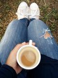 Kvinnahållkopp av varmt kaffe i henne händer ovanför sikt Jeans flåsar, vita skor, kallt väder royaltyfri foto