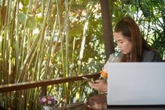 Kvinnahållmobiltelefon och dricka med is te i coffee shop, la arkivbilder