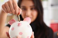 Kvinnahållpiggybank i armar satte pengar in i moneybox Arkivfoton