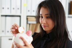 Kvinnahållpiggybank i armar satte pengar in i moneybox Arkivbild