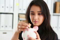 Kvinnahållpiggybank i armar satte pengar in i moneybox Royaltyfria Bilder
