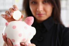 Kvinnahållpiggybank i armar satte pengar in i moneybox Arkivfoto
