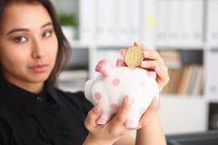 Kvinnahållpiggybank i armar satte pengar in i moneybox Royaltyfria Foton