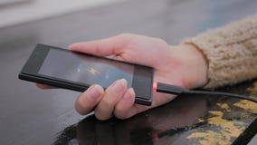 Kvinnahållsmartphone med den låga batterisymbolen på skärmen Arkivfoto