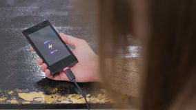 Kvinnahållsmartphone med den låga batterisymbolen på skärmen Arkivfoton