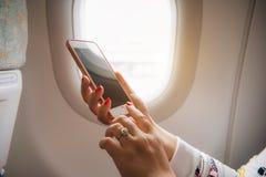 Kvinnahand genom att använda den smarta telefonen på flygplanet Kvinnligt använda för handelsresande royaltyfri bild