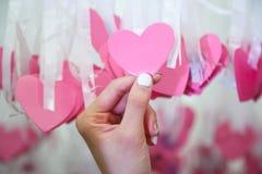Kvinnahand - rosa hjärtaform Lucky Draw som för hacka fästas till det vita bandet på att önska trädet i välgörenhethändelse Lekar royaltyfria bilder
