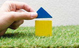 Kvinnahand som bygger ett litet hus med färgrika träkvarter Royaltyfri Fotografi