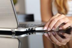 Kvinnahand som hemma pluggar en usb som är pendrive på en bärbar dator Royaltyfri Bild