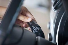 Kvinnahand som kontrollerar pinnen för kontroll för torkare för bilregnvindruta Royaltyfri Fotografi