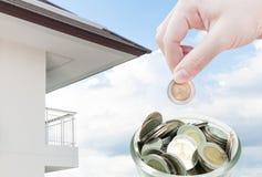 Kvinnahand som på sätter ett mynt, sparande, donationinvestering, mynt i besparingar för handpengar och lägenheten Arkivfoton