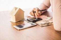 Kvinnahand som räknar pappers- valuta för pengar med den smarta telefonen, husmodellen och räknemaskinen på skrivbordet och att h arkivbilder