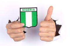 Kvinnahand som rymmer den Nigeria flaggan Royaltyfri Bild