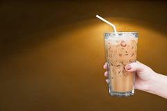 Kvinnahand som rymmer det glass med is kaffet på den bruna grungy väggen arkivbild