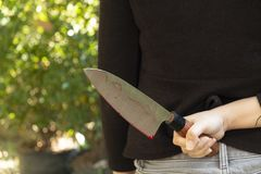 Kvinnahand som rymmer en blodig kniv på en svart bakgrund, socialt våldallhelgonaaftonbegrepp, foto av den seriella djävulska mör royaltyfri fotografi