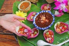 Kvinnahand som rymmer en nya Lotus Petal Savory Wrapped Called Miang kham i thailändskt språk royaltyfria bilder