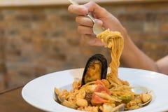 Kvinnahand som rymmer läcker spagetti på gaffel Arkivbilder