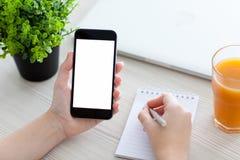 Kvinnahand som rymmer telefonen och skriver i en anteckningsbok royaltyfria foton