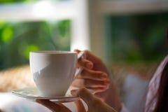 Kvinnahand som rymmer varmt kaffe Arkivbild