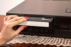 Kvinnahand som sätter in den tomma VHS kassetten i gammal videoregistreringsapparat arkivfoto