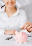 Kvinnahand som sätter myntet in i den lilla spargrisen Arkivfoto