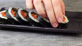 Kvinnahand som sätter stycken av koreansk maträttgimbap eller kimbap med tonfisk och grönsaker på plattan lager videofilmer