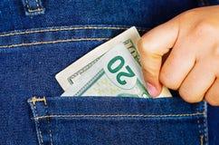 Kvinnahand som sätter tjugo dolars inom av jeansbakfickan Arkivfoton
