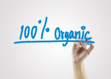 Kvinnahand som skriver organisk 100% på grå bakgrund för affär Fotografering för Bildbyråer