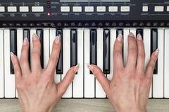 Kvinnahand som spelar ett slut för synt för MIDI kontrollanttangentbord upp Arkivbild