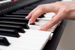 Kvinnahand som spelar ett slut för synt för MIDI kontrollanttangentbord upp Arkivbilder