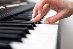 Kvinnahand som spelar ett slut för synt för MIDI kontrollanttangentbord upp Arkivfoton