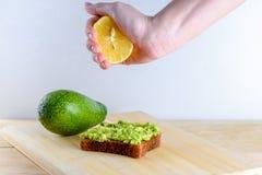 Kvinnahand som till hälften pressar av citronen på avokadorostat bröd för helt bröd royaltyfria bilder