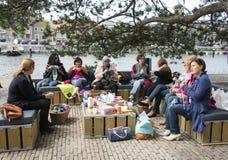 Kvinnahandarbete på en soffa utanför på multiculturedag i holland royaltyfria foton