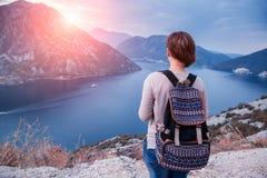 Kvinnahandelsresande med ryggsäcken på klippan Arkivfoton