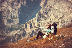 Kvinnahandelsresande med ryggsäcken som kopplar av i berg Royaltyfri Foto
