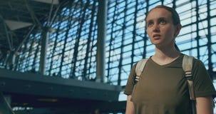 Kvinnahandelsresande p? flygplatsen som ser funktionskort-avvikelserna som s?ker efter ditt flyg arkivfilmer