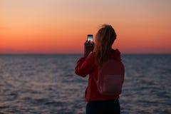 Kvinnahandelsresande som använder smartphonen och tar fotoet av den färgrika havssolnedgången Royaltyfri Foto