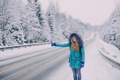 Kvinnahandelsresande som fångar bilen i vinterskog Royaltyfria Bilder