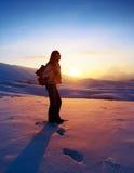 Kvinnahandelsresande som fotvandrar i vinterberg Arkivfoton