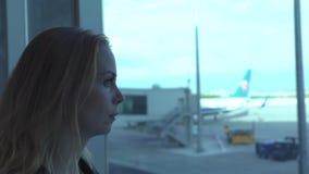 Kvinnahandelsresande som ser till det slutliga fönstret för flygplats på flygplanet i avvikelsevardagsrum Ung flicka som ser till lager videofilmer