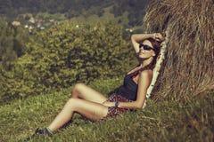 Kvinnahandelsresande som vilar nära en höstack Fotografering för Bildbyråer