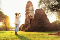 Kvinnahandelsresanden tar ett foto av den atcient Wat Chaiwatthanaram Buddhist templet i den heliga staden Ayutthaya, Thailand arkivbilder