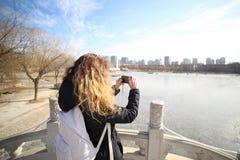 Kvinnahandelsresanden tar ett foto av landskapet av staden nära sjön i parkera med en ryggsäck Arkivbilder